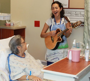 Danielle DeCosmo, an artist-in-residence at Shands Hospital at the University of Florida in Gainesville, sings for a patient (courtesy of Shands Arts in Medicine)